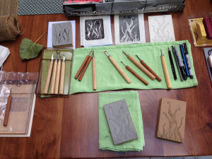 Carving images into linoleum blocks, which will then be printed.